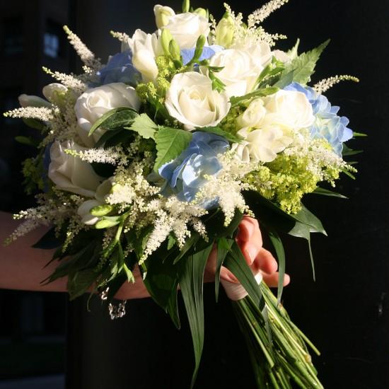 Ramo de novia clásico con rosas blancas y flor de temporada en tonos azules.